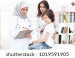 an arab woman doctor writes a... | Shutterstock . vector #1019591905