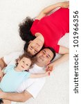 Young family with one child lying on the floor - top view - stock photo