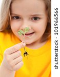 The wonder of life - little girl holding small seedling, closeup - stock photo