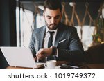 attractive suited man checking... | Shutterstock . vector #1019749372