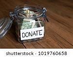 donate note on money jar  ... | Shutterstock . vector #1019760658