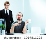 Small photo of An effeminate male office worker wearing bright red lipstick sitting at his desk simpering watched in disgust by a colleague in a smart suit and tie