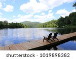 adirondack chairs on the river... | Shutterstock . vector #1019898382