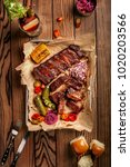 Small photo of Grilled pork ribs served with grilled corn, salat, bbq sauce, salt pepper and cucumber on parchment paper on a wooden table. Top View