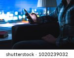 Small photo of Man using mobile phone home late at night. Guy looking messages with modern cellphone in dark. Unfaithful husband cheating and texting with another woman. Secret or illegal business. Sitting on couch.
