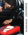 Small photo of Anti theft system problem concept. Burglar thief man wearing black clothes breaking into car, stealing smartphone and red shopping bag