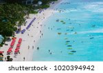 People who swim in Tumon beach in Guam from a high place, take a paddle board, and relax under colorful umbrellas. American Guam.