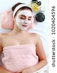 Small photo of Woman enjoying white spa mack,scrub on face.Clean skin