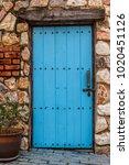 old blue wooden door in a stone ... | Shutterstock . vector #1020451126