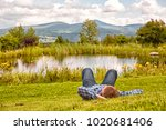 young guy lying in the grass by ... | Shutterstock . vector #1020681406