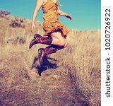 pretty woman in a skirt jumping ... | Shutterstock . vector #1020726922