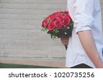 man holding bouquet of red... | Shutterstock . vector #1020735256