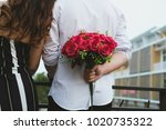 man holding bouquet of red... | Shutterstock . vector #1020735322
