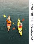 two men are kayaking along the... | Shutterstock . vector #1020801532
