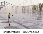 Boy Playing With A Fountain In...