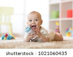 Stock photo cute baby boy drinking from bottle kid lying on carpet in nursery at home smiling child is 1021060435