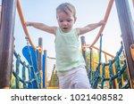 toddler boy walking on blue net ... | Shutterstock . vector #1021408582