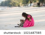 little girl playing with a cat... | Shutterstock . vector #1021687585
