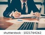 a man's hand holding pen... | Shutterstock . vector #1021764262