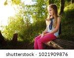 cute little girl sitting by the ... | Shutterstock . vector #1021909876