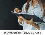 woman writing in her notebook. | Shutterstock . vector #1021967356