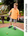 Young Boy Plays Mini Golf On...