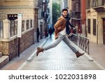young happy man jumping wearing ... | Shutterstock . vector #1022031898