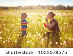 young woman with a boy blowing... | Shutterstock . vector #1022078575