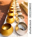 Small photo of Arrangement of Gold and silver alms bowl on the long table, To donate money to charity, coins in alms bowl