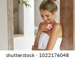 Small photo of Beautiful young woman with soft skin, has light hair tied in knot, wears white towel after taking douche, smells flower, looks down with happy expression, pleased after good relax at bathroom