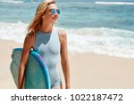 Small photo of Pretty restful female in sunglasses, satisfied with surfing riding, leaves seashore in good mood, has active recreation, fond of extreme sport, has pleased, happy expression. Tourism and rest concept