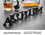 "Small photo of Composition with alcohol, handcuffs and word ""Alcoholism"" on grey table"
