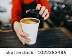 Small photo of Barista in apron is holding in hands hot cappuccino in white takeaway paper cup. Coffee take away at cafe shop