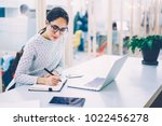 Stock photo pensive woman in eyewear planning working schedule writing in notebook while sitting at working 1022456278