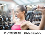 strong young woman pumping her... | Shutterstock . vector #1022481202