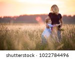 Small photo of Cute kid boy hugging his mother on a summer meadow on beautiful summer sunset. Happy family together. Mum and child. Motherhood and childhood. Family walking in the field. Outdoors.