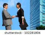 Young Business couple shaking hands over deal outdoors. - stock photo