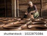 a woman potter in a plaid shirt ... | Shutterstock . vector #1022870386