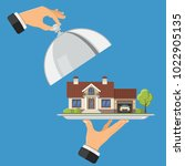 hand holds new house on tray....   Shutterstock .eps vector #1022905135