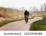 Cyclist On A Curved Country...