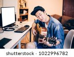 Young Asian man learning how to play guitar on computer monitor. Male guitarist watching online tutorial. Include clipping path on monitor - stock photo