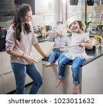 young mother cooking with her... | Shutterstock . vector #1023011632