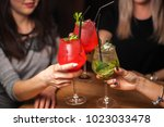 Small photo of Close up of girls drinking cocktails in nightclub. Girls having good time,cheering and drinking cold cocktails, enjoying friendship together in bar, close up view on hands.
