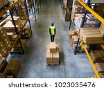 male warehouse worker pulling a ... | Shutterstock . vector #1023035476