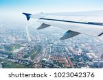 Small photo of aeroplane wing look from aeroplane window that flying above the city area