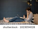 Side view  portrait of teenage boy doing homework while lying on bed, using laptop and speaking by phone at same time