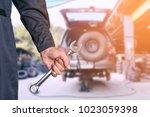 car repairman wearing a dark... | Shutterstock . vector #1023059398