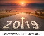 Small photo of Driving on idyllic open road against the setting sun forward to new year 2019. Concept for success and future.
