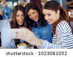 three young happy women doing... | Shutterstock . vector #1023081052