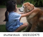 a girl playing with her old... | Shutterstock . vector #1023132475